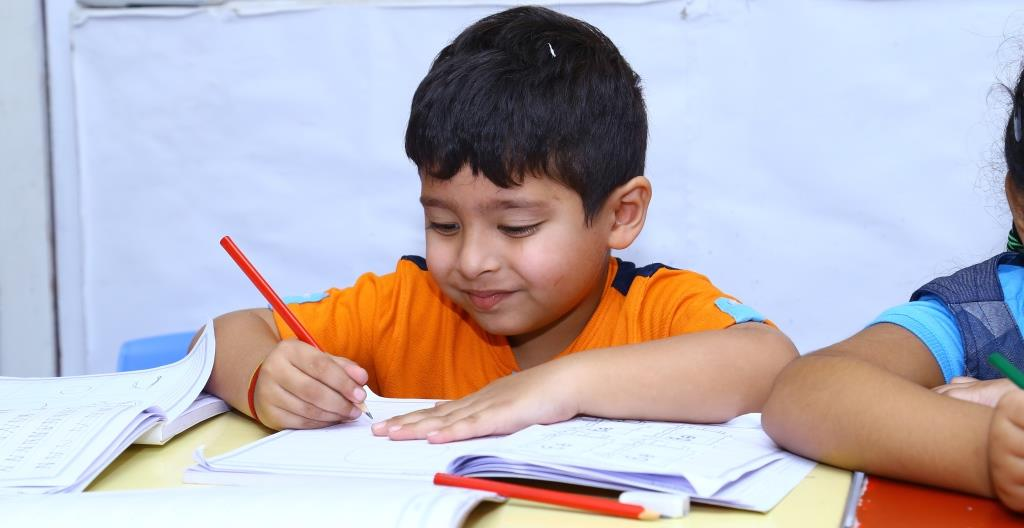 Children writing skills, Children Holding a pencil, Children Smile, Children writing Photos, Children Hyderabad, Children Bangalore